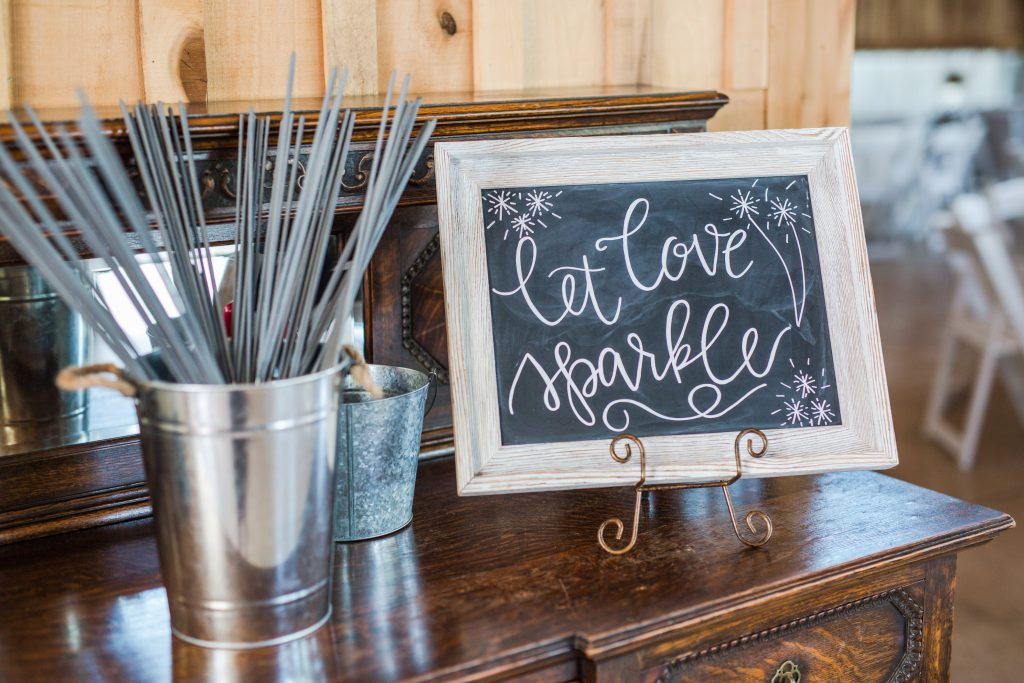 "Rustic barn wedding meets vintage fairy tale. Meadow Creek Farm North Alabama wedding venue. Vintage Beauty and the Beast inspired wedding reception decoration ideas. Lace, mermaid style wedding gown. Half up curly bridal hair with braids. Wedding chalkboard sign. ""Let love sparkle"" wedding reception chalkboard sign for sparkler send off"