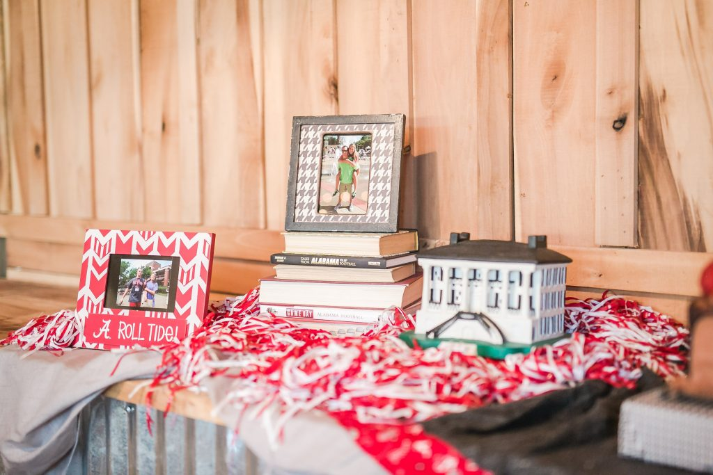 Rustic barn wedding meets vintage fairy tale. Meadow Creek Farm North Alabama wedding venue. Vintage Beauty and the Beast inspired wedding reception decoration ideas. Lace, mermaid style wedding gown. Half up curly bridal hair with braids. Groom's cake table. Alabama crimson tide groom's cake and table decor