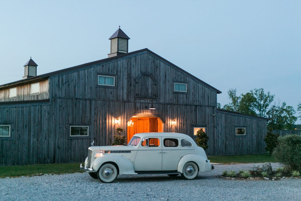 Rustic barn wedding meets vintage fairy tale. Meadow Creek Farm North Alabama wedding venue. Vintage Beauty and the Beast inspired wedding reception decoration ideas. Lace, mermaid style wedding gown. Half up curly bridal hair with braids. Vintage getaway car for wedding