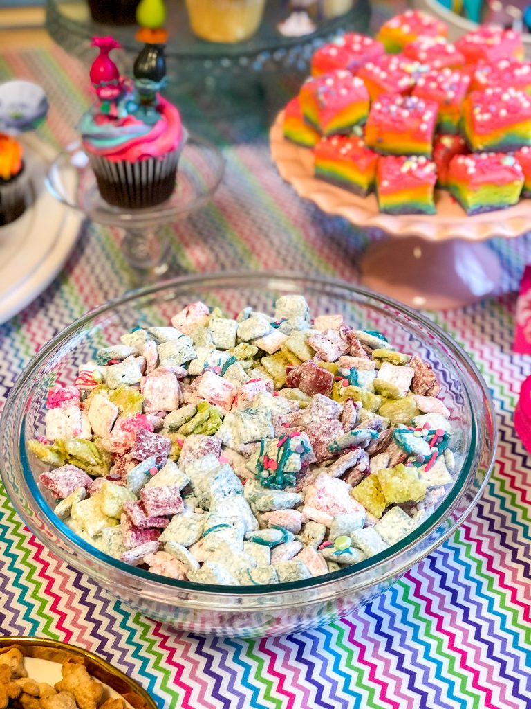 Rainbow Muddy Buddies. Rainbow muddy buddies recipe is perfect for Trolls birthday party, Unicorn birthday party, rainbow birthday party. Trolls birthday party food ideas. Unicorn birthday party food ideas. Rainbow food ideas